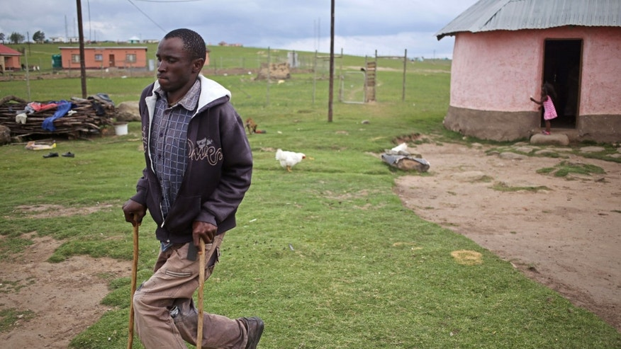 Malwande Mazwi a polio victim walks with sticks outside his home in Qunu, South Africa, Monday, Dec. 9, 2013. The home  where Nelson Mandela grew up had mud walls, a grass roof, and a floor polished smooth with cow dung. That was in the 1920s. When people flood Mandela's village on Sunday for the former president's burial, they will be in a place that _ except for a gleaming new highway and a strong cellphone network lags decades behind the  developed world.  (AP Photo/Schalk van Zuydam)