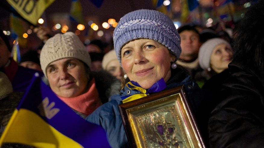 Pro-European Union activists holding a Ukrainian national flag and an icon listen to a speaker during a rally in Independence Square in Kiev, Ukraine, Thursday, Dec. 12, 2013. Ukraine's President Viktor Yanukovych appears to be in a tough corner. As protesters furious over his decision to turn away from the EU clog the center of Kiev, he appears to be leaving his options open for the best deal he can get from his economically troubled country's powerful suitors. (AP Photo/Alexander Zemlianichenko)