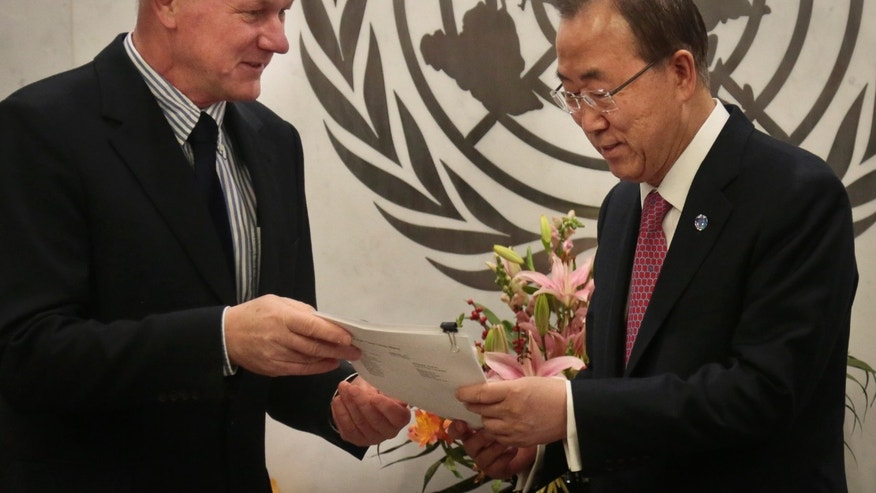 Prof. Ake Sellström, lead, head of the U.N. mission to investigate allegations of the use of chemical weapons in the Syria, hands U.N. Secretary Ban Ki-moon a report on the investigation on Thursday, Dec. 12, 2013, at U.N. headquarters. (AP Photo/Bebeto Matthews)