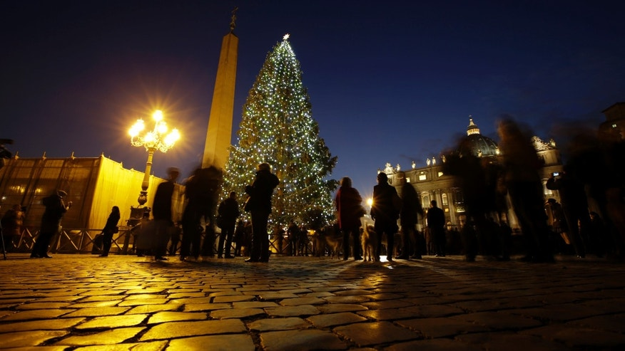 People stop to look at the Christmas tree next to St. Peter's Basilica in St. Peter's Square at the Vatican, Friday, Dec. 13, 2013. The 25-meter (82 feet) tall tree which arrived from Bavaria, Germany was lit Friday evening at the end of ceremony. Big crowds are expected to flock to the square during the holidays to admire the tree. (AP Photo/Andrew Medichini)