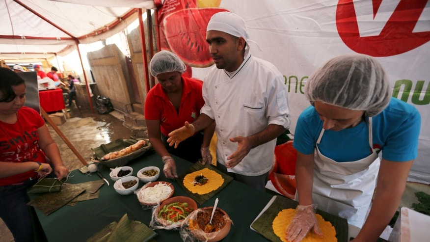 In this Nov. 23, 2013 photo, a chef demonstrates how corn dough tamales known as hallacas are prepared, at a Christmas fair in a state-owned market in Caracas, Venezuela. The country's most-enduring Christmas traditions: the gathering of family to prepare hallacas, is under threat from the nation's grinding economic crisis. With inflation near a two-decade high of 54 percent, prices for many of the treat's trademark ingredients have skyrocketed beyond the reach of many family budgets. (AP Photo/Fernando Llano)