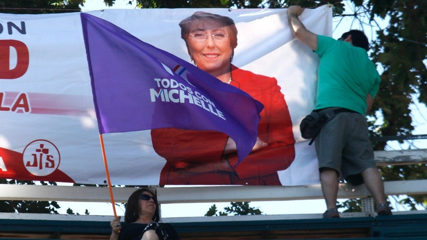 In this Dec. 12 photo, a man adjusts a banner of Presidential candidate Michelle Bachelet before a closing campaign rally in Santiago, Chile. Bachelet is almost certain to win Sunday's presidential runoff and return to power on a promise to reduce Chile's huge gap between the rich and poor.  (AP Photo/ Luis Hidalgo)