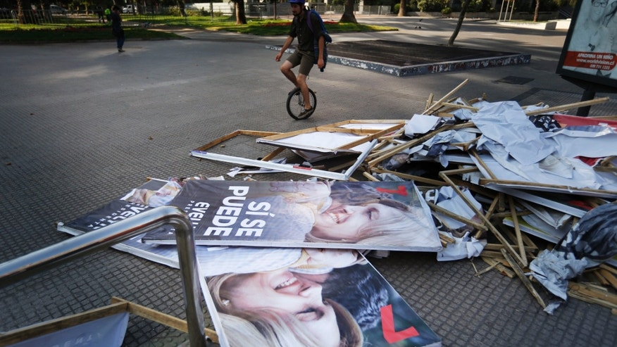 A uni-cyclist passes next to discarded posters of presidential candidate Evelyn Matthei in Santiago, Chile, Saturday, Dec. 14, 2013. Next Sunday, Matthei will face Michelle Bachelet, who became Chile's first female president from 2006 to 2010.  (AP Photo/Jorge Saenz)