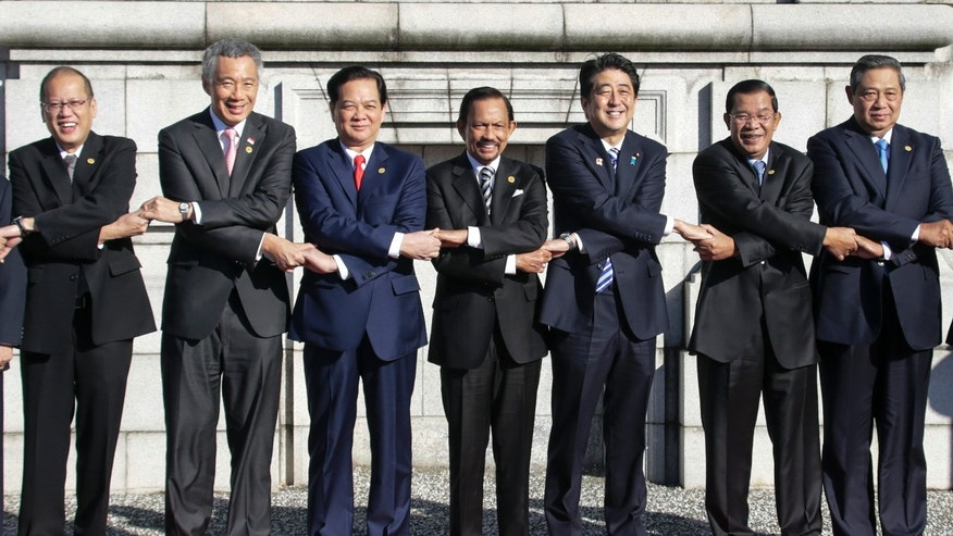 Japanese Prime Minister Shinzo Abe, third right, and leaders of ASEAN countries join hands for a photo session of Japan-ASEAN commemorative summit at Akasaka State Guesthouse in Tokyo, Japan, Saturday, Dec. 14,  2013. Leaders from left: Philippine President Benigno Aquino III, Singaporean Prime Minister Lee Hsien Loong, Vietnamese Prime Minister Nguyen Tan Dung, Brunei's Sultan Hassanal Bolkiah,  Abe, Cambodian Prime Minister Hun Sen and Indonesian President Susilo Bambang Yudhoyono. (AP Photo/Kimimasa Mayama, Pool)