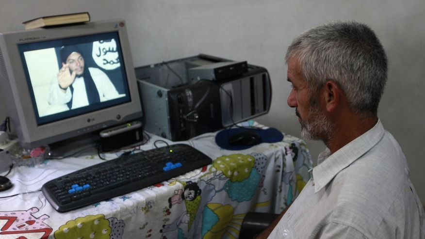 In this Monday, Nov. 11, 2013 photo, Jihad Zaaneen looks at a picture of his 22-year-old son, Mohammed Zaaneen, on his home computer in Beit Hanoun, northern Gaza Strip. Mohammed died Sept. 17 in a suicide attack in Syria claimed by an al-Qaida-linked group, the Islamic State in Iraq and the Levant. Zaaneen's journey to martyrdom in Syria had a peculiar twist. He found himself at odds with another Islamic militant group with a long history of suicide attacks, Gaza's ruling Hamas. Hamas carried out scores of suicide attacks in Israel since the mid-1990s. But it rejects global jihad, focusing on the fight against Israel. (AP Photo/Hatem Moussa)