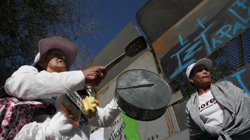 FILE - In this Dec. 8, 2013 file photo, demonstrators bang pots during a protest against the energy reform bill outside the Mexican Senate building in Mexico City, Sunday, Dec. 8, 2013. The opening of Mexico's oil industry to private and foreign investment caps a remarkable series of legislative victories by President Enrique Pena Nieto, who is trying to re-engineer the country's most dysfunctional institutions. (AP Photo/Marco Ugarte, File)