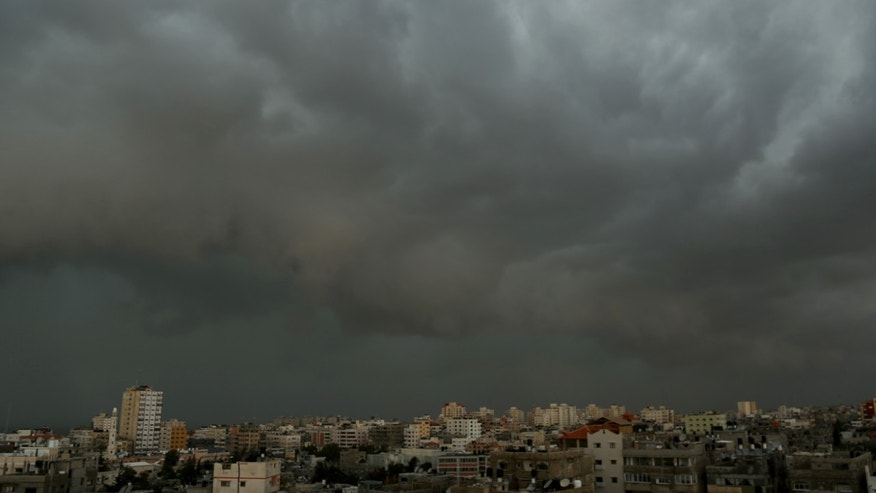 Dark clouds overcasts Gaza City, Friday, Dec. 13, 2013. Early snow has surprised many Israelis and Palestinians as a blustery storm, dubbed Alexa, brought gusty winds, torrential rains and heavy snowfall to parts of the Middle East. (AP Photo/Hatem Moussa)