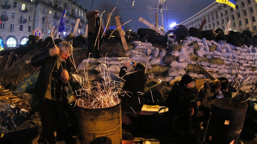 A pro-European Union activists works on a bonfire near a barricade in the Independence Square in Kiev, Ukraine early Saturday, Dec. 14, 2013. Ukraine's president proposed an amnesty Friday for all protesters facing criminal charges in the country's wave of massive anti-government demonstrations. President Viktor Yanukovych made the offer at a round-table meeting that included three leaders of the opposition that has orchestrated more than three weeks of anti-government protests, flooding the streets of Kiev with hundreds of thousands of people. (AP Photo/Dmitry Lovetsky)