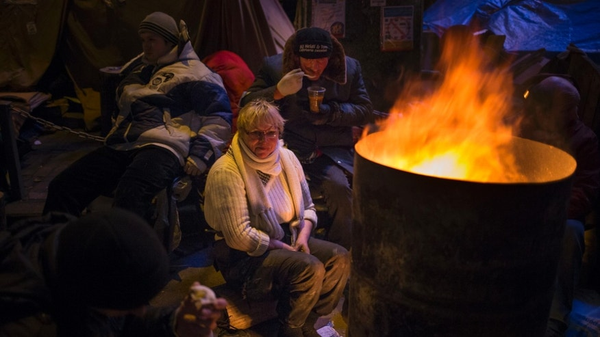 Remaining on duty overnight volunteers warm themselves at a bonfire at a Pro-European Union's tent camp in the Independence Square in Kiev, Ukraine, Saturday, Dec. 14, 2013. The opposition has called for a vast turnout Sunday. Rallies on the previous two Sundays drew hundreds of thousands of protesters. That same day, Yanukovych's Party of Regions has called for a pro-government demonstration that it claims will bring 200,000 people to Kiev. (AP Photo/Alexander Zemlianichenko)