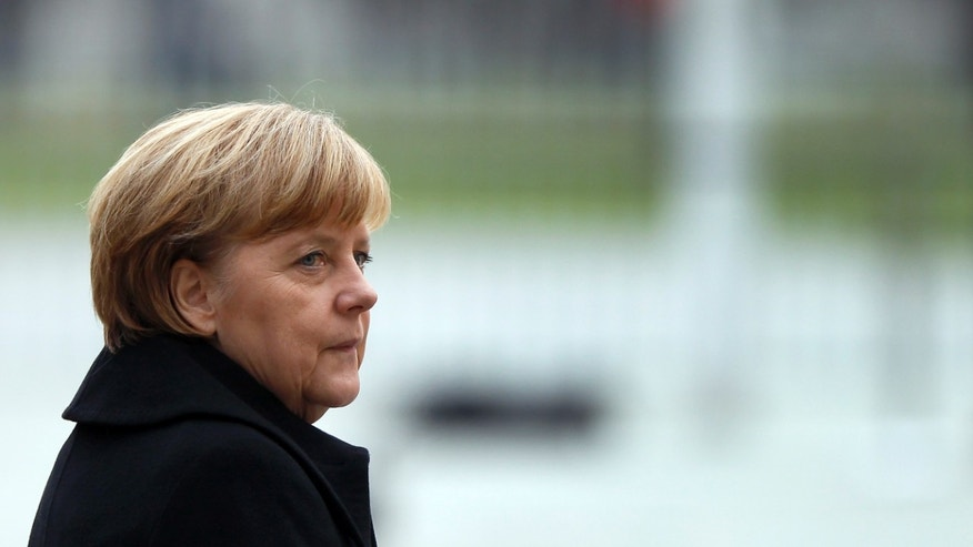 German Chancellor Angela Merkel attends a military welcome ceremony for the President of Mali Ibrahim Boubacar Keita, at the chancellery in Berlin, Germany, Wednesday, Dec. 11, 2013. (AP Photo/Michael Sohn)