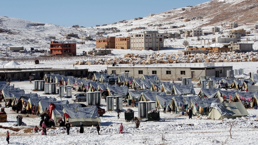 Syrian refugees walk outside their tents at a refugee camp in the eastern Lebanese border town of Arsal, Lebanon, Sunday, Dec. 15, 2013. Tens of thousands of impoverished Syrian refugees living in tents, shacks and unfinished buildings throughout Lebanon face a miserable winter as aid organizations scramble to meet their needs, constantly overwhelmed by ever-more Syrians fleeing their country's war. Charities have already distributed blankets, mattresses, kerosene heaters, winter clothes and coupons for fuel ahead of the region's unprecedented storm this week that blanketed parts of Lebanon, the Palestinian Territories, Turkey, Israel and even Egypt's deserts with snow, amid icy and rainy winds. (AP Photo/Bilal Hussein)