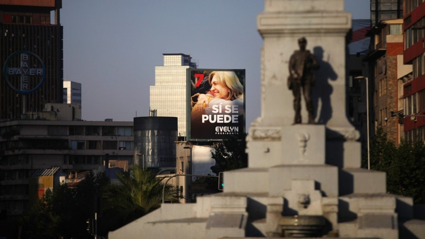 A large outdoor banner of presidential candidate Evelyn Matthei is displayed as seen from Baquedano square in Santiago, Chile, Saturday, Dec. 14, 2013. Matthei will face Michelle Bachelet, who became Chile's first women president from 2006 to 2010. (AP Photo/Jorge Saenz)