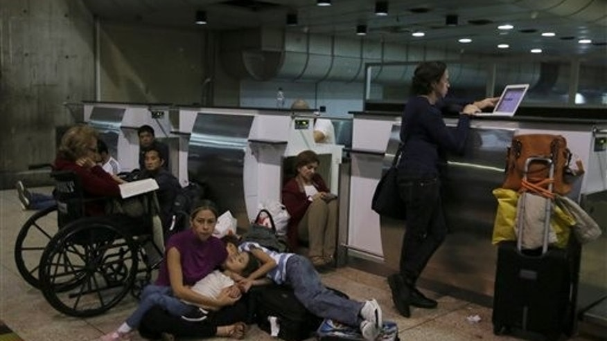 Passengers lie on the ground after their  Air France flight 385 to Paris was called at Simon Bolivar Airport in Maiquetia near  Caracas, Venezuela, Sunday, Dec. 15, 2013. Venezuelan bomb experts are inspecting a grounded Air France flight after being tipped off by French authorities that a terrorist group may be planning to detonate an explosive device in midair. Venezuelan Interior Minister Miguel Rodriguez Torres told state TV that a team of more than 60 technicians are performing an exhaustive search of the aircraft that will take several hours before the flight can be rescheduled. (AP Photo/Fernando Llano)