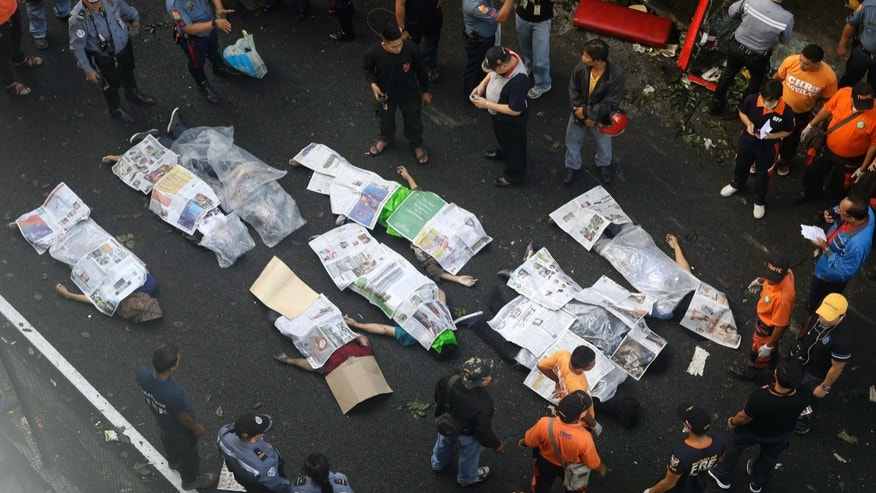Bodies of passengers are covered in newspapers as they are laid down on the road after a passenger bus plunged from an elevated highway known as the Skyway Monday, Dec. 16, 2013, in suburban Paranaque southeast of Manila, Philippines. Officials said at least 21 people died, mostly passengers, and more than 20 others were injured in the accident. (AP Photo/Bullit Marquez)