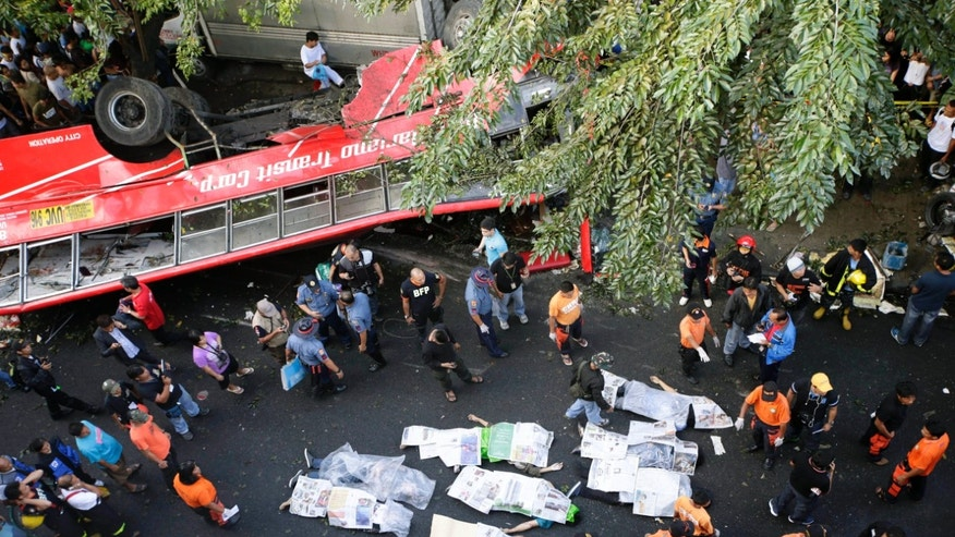 Bodies of passengers are covered in newspapers as they are laid down on the road after a passenger bus plunged from an elevated highway known as Skyway Monday, Dec. 16, 2013, in suburban Paranaque southeast of Manila, Philippines. Officials said at least 21 people died, mostly passengers, and more than 20 others were injured in the accident. (AP Photo/Bullit Marquez)