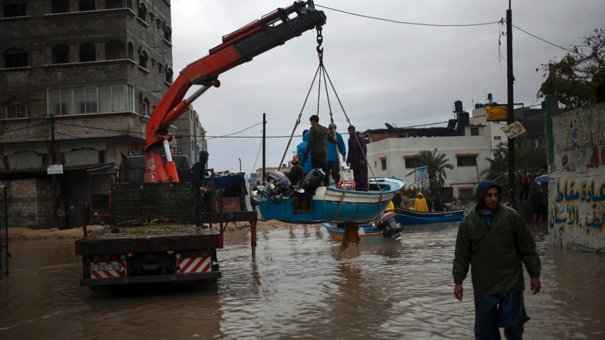 Palestinian rescue members evacuate residents using fishing boats following heavy rains in Gaza City, Saturday, Dec. 14, 2013. Rescue workers evacuated more than 5,000 Gaza Strip residents from homes flooded by four days of heavy rain, using fishing boats and heavy construction equipment to pluck some of those trapped from upper floors, an official said Saturday. (AP Photo/Khalil Hamra)