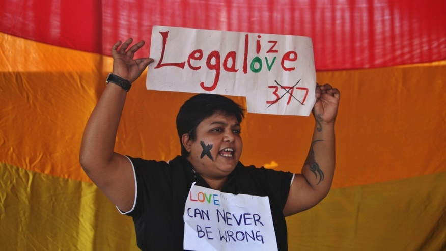 An Indian gay rights activist holds a placard during a protest against a Supreme Court verdict that upheld section 377 of the Indian Penal Code that criminalizes homosexuality in Hyderabad, India, Sunday, Dec. 15, 2013. The Supreme Court ruled Wednesday that only lawmakers could change a colonial-era law that bans same-sex relations and makes them punishable by up to a decade in prison. (AP Photo/Mahesh Kumar A.)