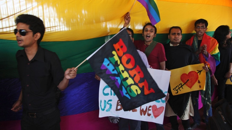 Indian gay rights activists hold placards and wave flags during a protest against a Supreme Court verdict that upheld section 377 of the Indian Penal Code that criminalizes homosexuality in Hyderabad, India, Sunday, Dec. 15, 2013. The Supreme Court ruled Wednesday that only lawmakers could change a colonial-era law that bans same-sex relations and makes them punishable by up to a decade in prison. (AP Photo/Mahesh Kumar A.)