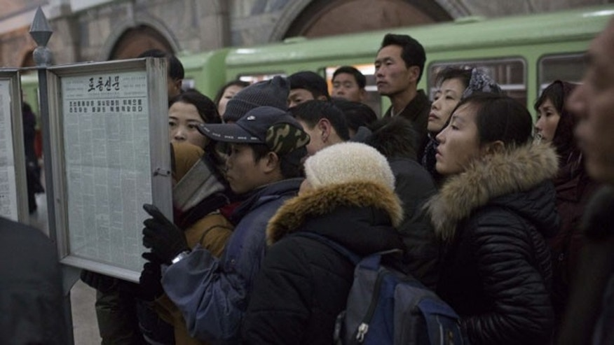 December 13, 2013: North Korean subway commuters gather around a public newspaper stand on the train platform in Pyongyang to read the headlines about Jang Song Thaek, North Korean leader Kim Jong Un's uncle who was executed as a traitor. (AP Photo/David Guttenfelder)