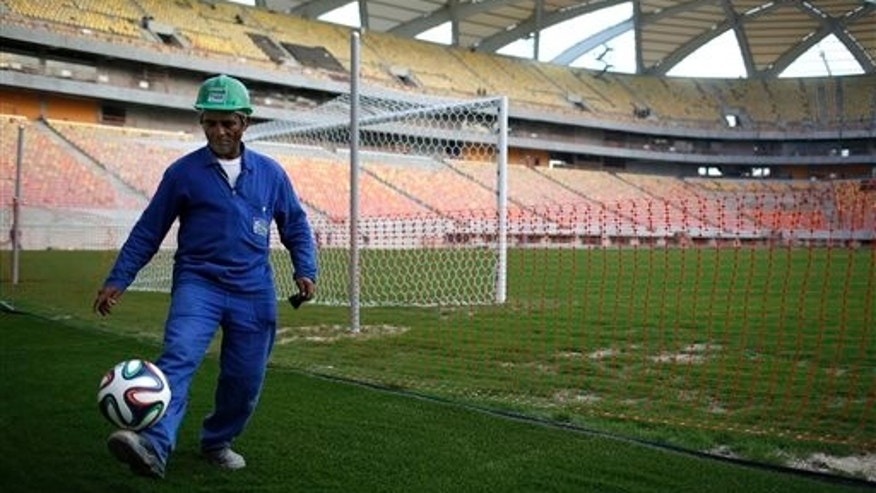 In this Dec. 10, 2013 photo, construction worker Cicero Nogueira de Almeida plays with a ball at the Arena da Amazonia stadium, in Manaus, Brazil. The construction firm building the Arena da Amazonia stadium which will host World Cup games in the jungle city of Manaus says a worker fell to his death Saturday from the stadium's roof structure. The Andrade Gutierrez company says Marcleudo Ferreira fell some 115 feet. (AP Photo/Renata Brito)
