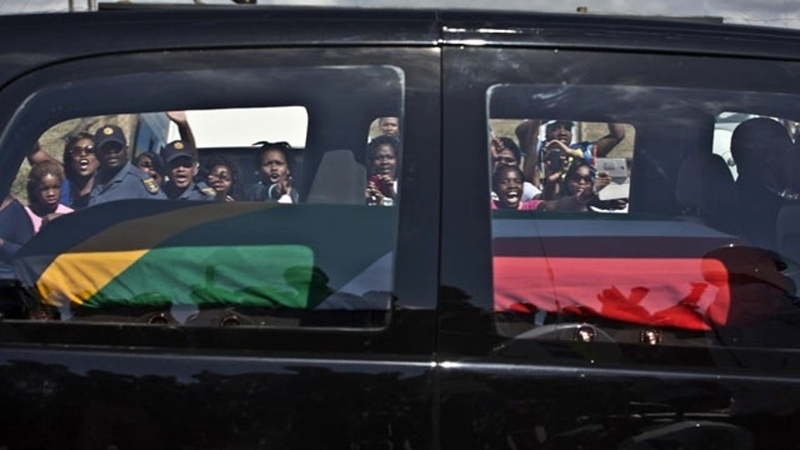 December 14, 2013: South African mourners wave and cheer as the hearse transporting the body of Former President Nelson Mandela passes through the town of Mthatha on its way to Qunu, South Africa. (AP Photo/Muhammed Muheisen)