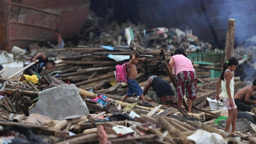 Dec. 7, 2013: A boy survivor carries a school bag as he walks by debris from damaged homes at typhoon ravaged Tacloban city, central Philippines.