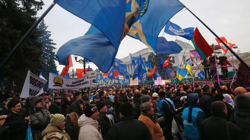 Supporters of Yanukovych's party of Regions wave their flags during a rally in Kiev, Ukraine, Sunday, Dec. 15, 2013. A much smaller rally of government supporters, about 15,000, was taking place about a kilometer away from Independence Square familiarly called Maidan, where anti-government protesters have set up an extensive tent camp and erected barricades of snow hardened with freezing water and studded with scrap wood and other junk.  (AP Photo/Sergei Grits)