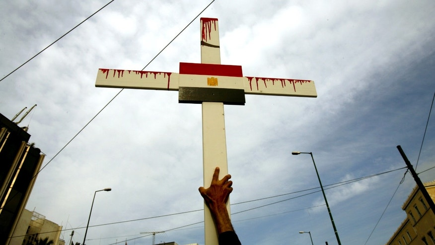 April 19, 2006 - FILE photo - An Egyptian Coptic Christian holds a cross with the Egyptian flag during a demonstration outside the Egyptian embassy in Athens. 3 Christians received long prison sentences Sunday for the death of a Muslim in sectarian clashes, but no one has been prosecuted in the deaths of at least five Coptics in the same street battle.