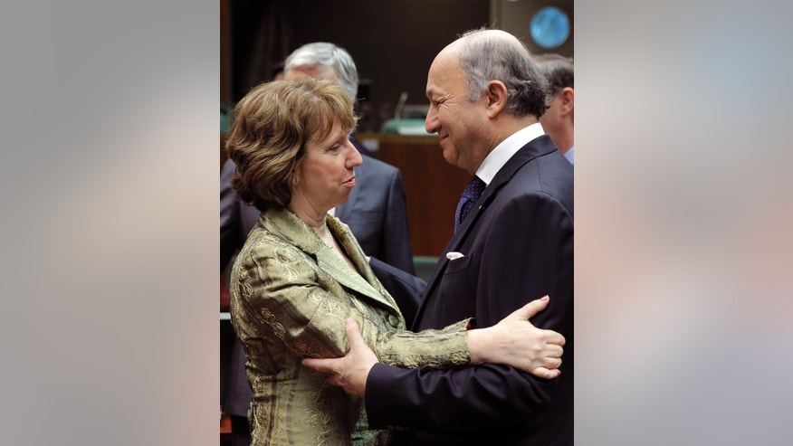 French Foreign Minister Laurent Fabius, right, talks with EU foreign policy chief Catherine Ashton, during the EU foreign ministers meeting, at the European Council building in Brussels, Monday, Dec. 16, 2013. European Union foreign ministers meeting Monday argue that the door remains open for Ukraine to sign an association agreement the EU, even though they criticized the delaying tactics and mixed messages sent by Ukraine President Viktor Yanukovych. (AP Photo/Yves Logghe)
