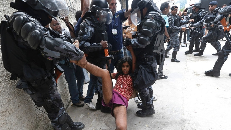 A supporter of indigenous people is carried away by police officers during a protest at the old Indian Museum, next to the Maracana stadium, in Rio de Janeiro, Monday, Brazil, Dec. 15, 2013. The Indian Museum has been at the center of a drawn-out legal battle between the several dozen indigenous who had been living there for years and state and local authorities. Officials initially wanted to raze the complex as part of renovations ahead of Brazil's 2014 World Cup. (AP Photo/Silvia Izquierdo)