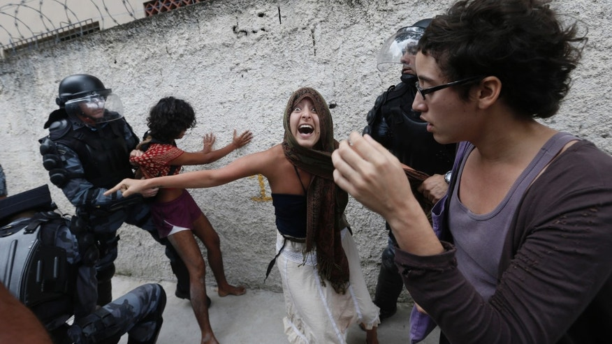 Supporter of indigenous people clash with police officers during a protest at the old Indian Museum, next to the Maracana stadium, in Rio de Janeiro, Monday, Brazil, Dec. 15, 2013. The Indian museum has been at the center of a drawn-out legal battle between the several dozen indigenous who had been living there for years and state and local authorities. Officials initially wanted to raze the complex as part of renovations ahead of Brazil's 2014 World Cup. (AP Photo/Silvia Izquierdo)