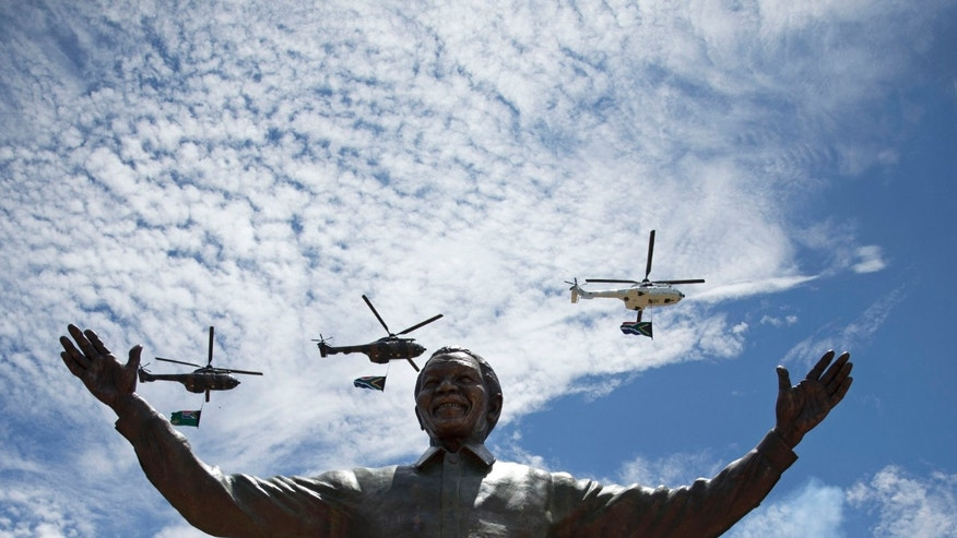 Helicopters perform a flypast as smoke rises from a gun salute after the unveiling of a 9 metre bronze statue of former South Africa President Nelson Mandela outside Union Buildings in Pretoria, South Africa, Monday, Dec. 16, 2013.  The statue was unveiled as part of the Day of Reconciliation Celebrations which occur annually on December 16 at the Union Buildings, which this year fall on the structure's centenary.  (AP Photo/Matt Dunham)