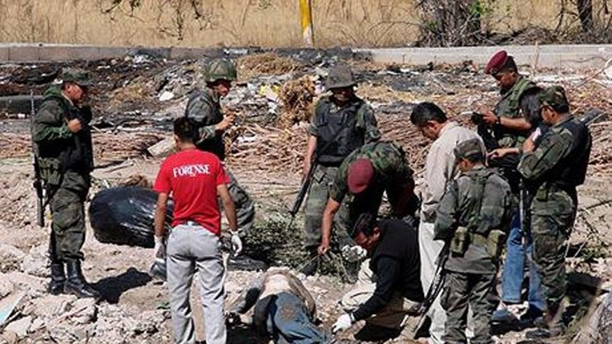 Police and forensic officers look at the body of U.S. Marshal Vicente Bustamante, found in the outskirts of Juarez, Mexico, Wednesday, March 25, 2009. (AP Photo)