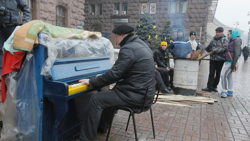 An activist plays the piano for Pro-European Union supporters which warm themselves near a bonfire in the city main street of Khreschatyk in Kiev Ukraine, Monday, Dec. 16, 2013. Ukraine's opposition appears confident and shows no sign of relenting in its standoff with the government. The government has made some gestures toward the opposition, rejected some of its main demands and is opaque on another.  (AP Photo/Efrem Lukatsky)