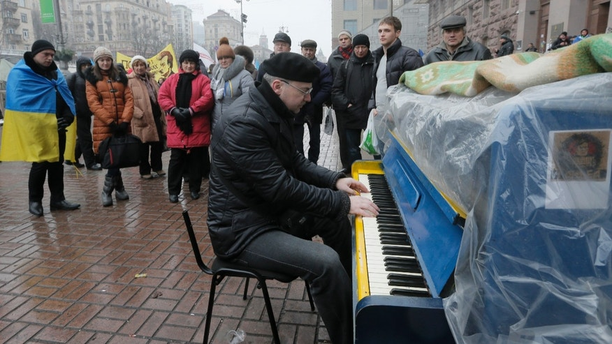 An activist plays the piano for Pro-European Union supporters  in the city main street of Khreschatyk in Kiev Ukraine, Monday, Dec. 16, 2013. Ukraine's opposition appears confident and shows no sign of relenting in its standoff with the government. The government has made some gestures toward the opposition, rejected some of its main demands and is opaque on another. (AP Photo/Efrem Lukatsky)