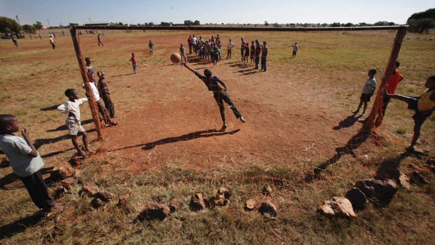 FILE - In this photo taken Tuesday May 25, 2010, children practice shooting at goals, at the Matikiring sports ground,near Lichtenburg, in the rural part of northern South Africa. South Africa's blacks have full political rights, but many remian deep in poverty despite substantial growth in the blacl middle calss. (AP Photo/Denis Farrell, File)