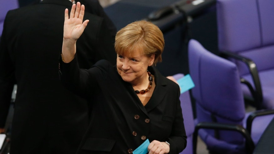 German Chancellor Angela Merkel waves while holding  the ballot in her hand during the Chancellor election at a meeting of the German federal parliament, Bundestag, in Berlin, Germany, Tuesday, Dec. 17, 2013. (AP Photo/Michael Sohn)