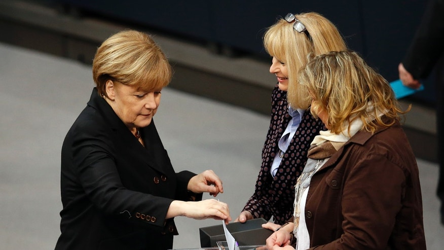 German Chancellor Angela Merkel casts her vote for the Chancellor election during a meeting of the German federal parliament, Bundestag, in Berlin, Germany, Tuesday, Dec. 17, 2013. (AP Photo/Michael Sohn)