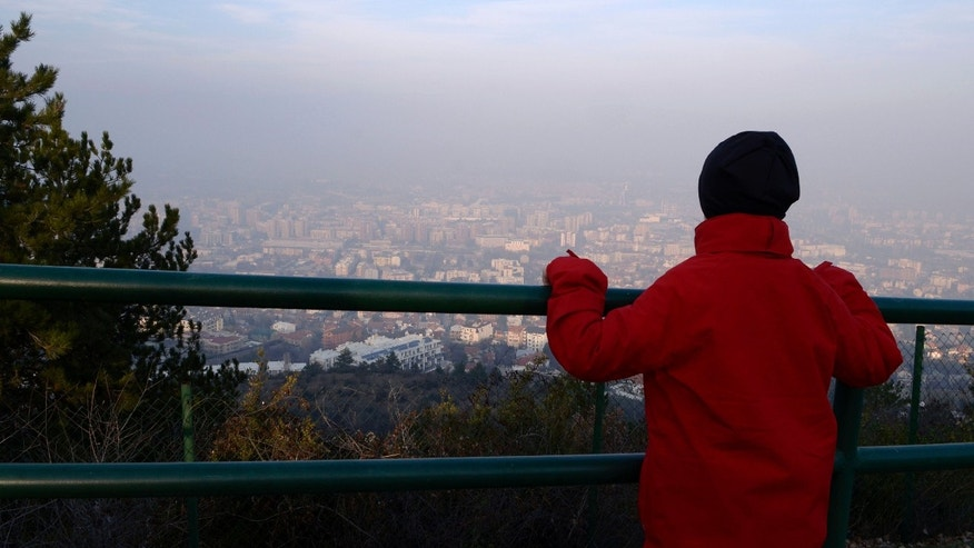 In this picture taken on Sunday, Dec. 15, 2013, a boy looks at the polluted air over Macedonia's capital Skopje, from Vodno Mountain just above the city.  Six days of high levels of harmful air pollution has forced Macedonian government on Tuesday to order companies and state institutions in four regions, including capital Skopje, to exempt from work pregnant woman and people over 60 years of age. (AP Photo/Boris Grdanoski)