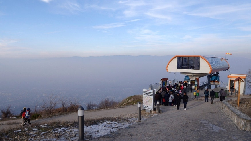 In this picture taken on Sunday, Dec. 15, 2013, people board a ropeway on top of Vodno Mountain, on their way back to Macedonia's capital Skopje, seen below through a thick layer of polluted air. Six days of high levels of harmful air pollution has forced Macedonian government on Tuesday to order companies and state institutions in four regions, including capital Skopje, to exempt from work pregnant woman and people over 60 years of age. (AP Photo/Boris Grdanoski)