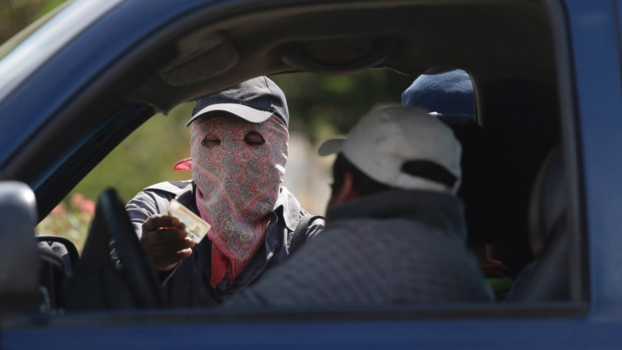 FILE - In this Jan. 18, 2013 file photo, a masked armed man checks the identity of a driver at a roadblock at the entrance to the town of El Pericon, near Ayutla, Mexico. Mexico's human rights body said Tuesday Dec. 17, 2013 the government shouldn't be allowing the formation of vigilante groups in some parts of Mexico where people have risen up to battle drug gangs. It says they could lead to more violence and undermine the rule of law. (AP Photo/Dario Lopez-Mills, File)