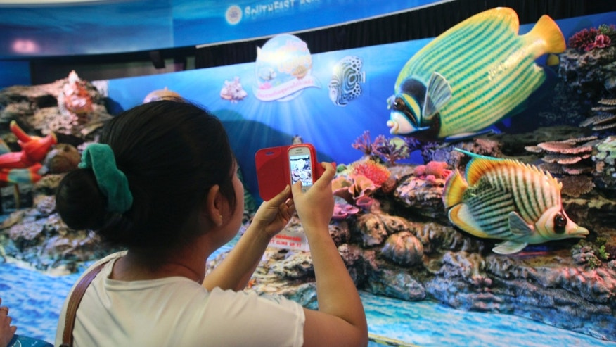 In this photo taken on Monday, Dec. 16, 2013, a visitor uses her mobile phone to take a picture of an aquatic animal display at Siam Ocean World,  located in Siam Paragon shopping mall in Bangkok Monday,  Dec. 16, 2013. Siam Paragon has claimed this year's crown as the world's most photographed location on Instagram. It edged out No. 2 Times Square and No. 3 Disneyland in California on the list that also includes New York's Central Park and Dodger Stadium in Los Angeles. (AP Photo/Sakchai Lalit)