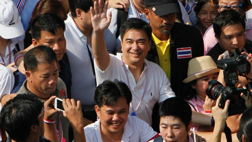 FILE - In this Monday, Dec. 9, 2013 file photo, Democrat leader and former Prime Minister Abhisit Vejjajiva, center, waves as he marches with anti-government protesters in Bangkok. Thailand's opposition Democrat Party has re-elected former Prime Minister Abhisit Vejjajiva its leader ahead of a crucial decision over whether to boycott an upcoming general election. Party spokesman Chavanond Intarakomalyasut confirmed Abhisit's selection Tuesday, Dec. 17, passed by almost unanimous vote. (AP Photo/Greg Baker, File)
