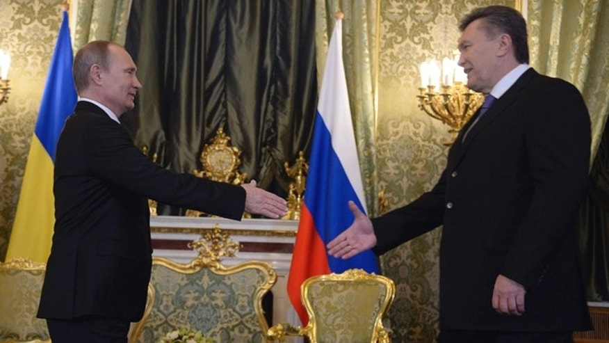 Dec. 17, 2013: Russian President Vladimir Putin, left, shakes hands with his Ukrainian counterpart Viktor Yanukovych during their meeting in Moscow.