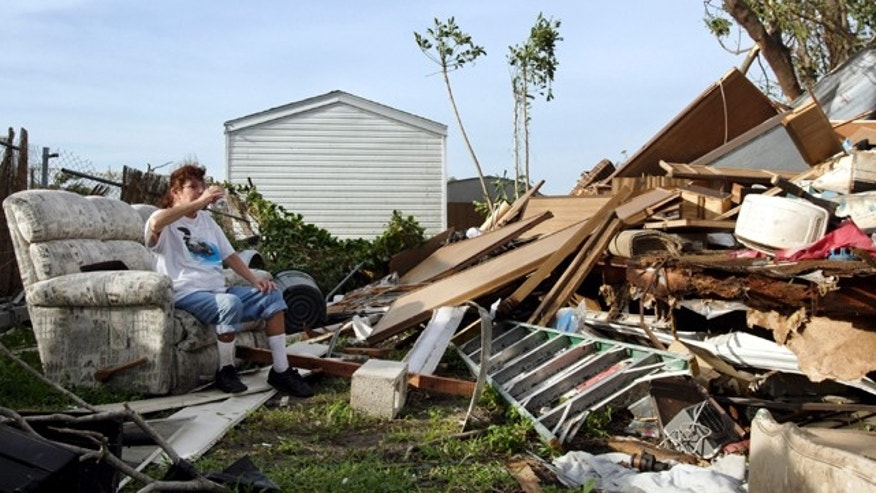 DAVIE, FL - OCTOBER 24:  Jennifer Farrington (L) sits on a couch in the middle of a pile of debris after Hurricane Wilma came through on October 24, 2005 in the Palma Nova motor home community in Davie, Florida. Hurricane Wilma hit the western coast of Florida as a Category Three and departed the eastern coast as a Category Two hurricane.  High winds from the fast moving hurricane have caused widespread power outages across the state.  (Photo by Richard Patterson/Getty Images)