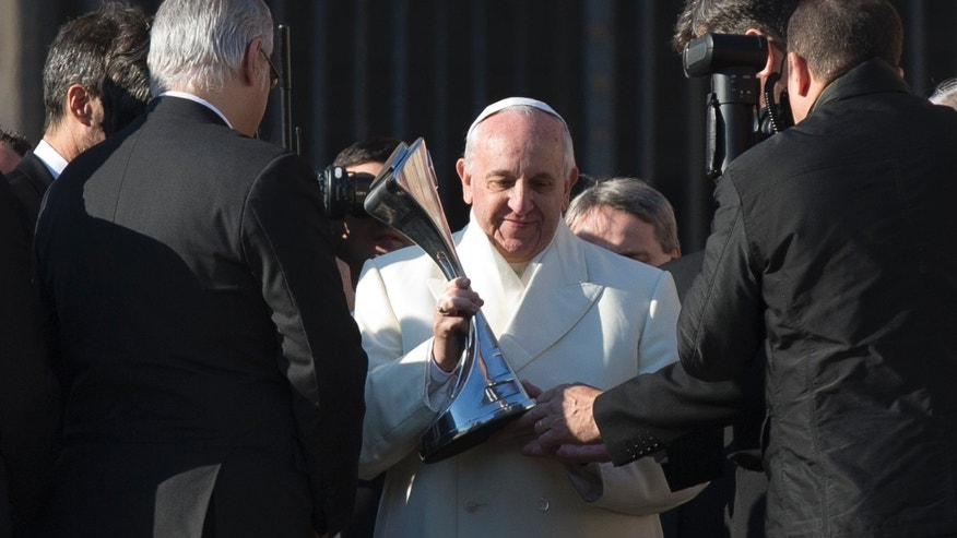 "Pope Francis looks at a replica of the Argentine soccer major league's trophy he was presented by a delegation of San Lorenzo soccer team, at the end of his weekly general audience in St. Peter's Square at the Vatican, Wednesday, Dec. 18, 2013. Pope Francis has celebrated his beloved San Lorenzo's victory in the Argentine soccer championship, hoisting up a replica of their trophy for all to see. A small group of team managers and players met with Francis on the steps of St. Peter's Basilica at the end of his Wednesday general audience. The group presented him with the replica of the trophy and a red and blue team jersey with ""Francisco Campeon"" written on back. A clearly pleased Francis raised the trophy for all to see. San Lorenzo, of which then-Cardinal Jorge Mario Bergoglio was a registered fan, clinched the Argentine championship Sunday. (AP Photo/Alessandra Tarantino)"