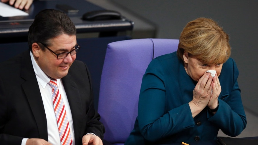 German Chancellor Angela Merkel, right, blows her nose as she sits beside German Economy and Energy Minister Sigmar Gabriel, left, during a meeting of the German federal parliament, Bundestag, in Berlin, Germany, Wednesday, Dec. 18, 2013. (AP Photo/Michael Sohn)