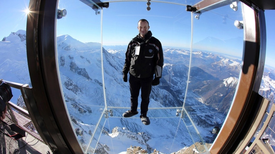 In this photo taken on Tuesday, Dec. 17, 2013, Mathieu Dechavanne, head of the Compagnie du Mont Blanc which runs the new attraction, stands in a glass cage named 'Pas dans le Vide' (Step into the Void) at the top of the Aiguille du Midi peak (3842-meters high or 12,604 feet), in the French Alps, during a press visit. Visitors can enjoy the view of Mont Blanc, Europe's highest mountain, from the platform. The attraction opens Saturday. (AP Photo/Alexis Moro)