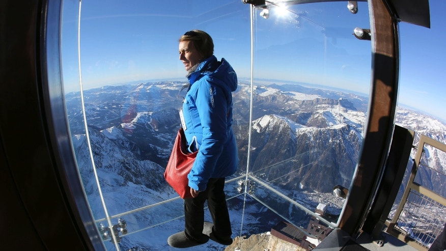 In this photo taken on Tuesday, Dec. 17, 2013, a reporter looks at the mountains through a glass cage named 'Pas dans le Vide' (Step into the Void) at the top of the Aiguille du Midi peak (3842-meters high or 12,604 feet), in the French Alps, during a press visit. Visitors can enjoy the view of Mont Blanc, Europe's highest mountain, from the platform. The attraction opens Saturday. (AP Photo/Alexis Moro)