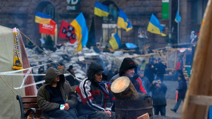 Pro-European Union activists warm themselves at a bonfire behind barricades while they guard the Independence Square in Kiev, Ukraine, Tuesday, Dec. 17, 2013. Weeks of angry pro-European Union protests as well as Western pressure have forced Yanukoyvch to make some concessions to the opposition. Last week Yanukovych called for an amnesty for some of the activists detained. (AP Photo/Sergei Grits)